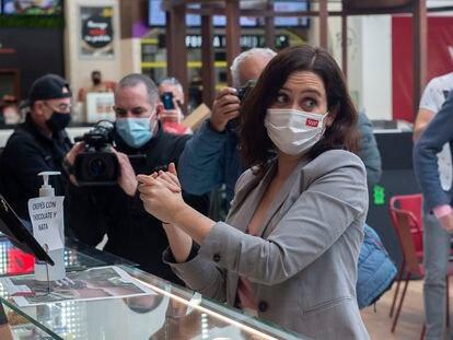 La presidenta de la Comunidad de Madrid, Isabel Díaz Ayuso, se lava las manos durante la presentación de la nueva zona de restauración del centro comercial  Intu Xanadú, en Arroyomolinos, Madrid (España).