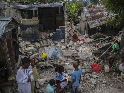 Una familia desayuna junto a su casa destruida por el terremoto del sábado en Les Cayes, Haití.
