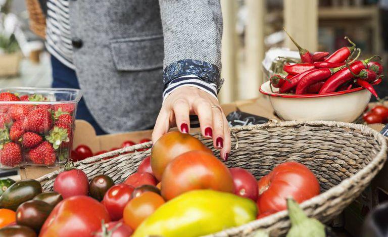 Una mujer coge un tomate de una cesta de verduras.