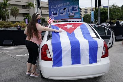 Una mujer pone una bandera cubana en su coche, en un mitin de Biden en Miami.