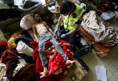 Youssef Bouzidi, un solicitante de asilo marroquí que está en huelga de hambre durante más de un mes, es examinado por un trabajador de la salud en una habitación en el campus de la universidad de Bélgica ULB, el 29 de junio de 2021.
