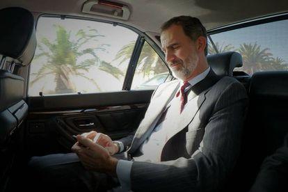 Don Felipe, con su teléfono móvil en el coche oficial.