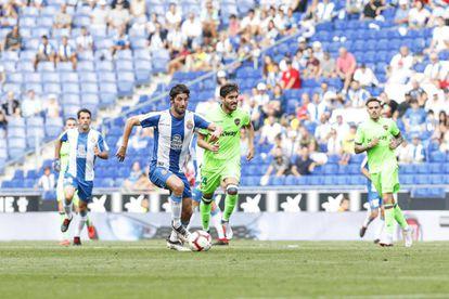 Granero conduce el balón con Campaña, del Levante, al lado.