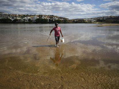 Un hombre camina por el lecho del río Doce.