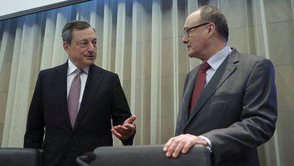 Al la izquierda, el presidente del Banco Central Europeo, Mario Draghi, conversa con el gobernador del Banco de España, Luis Linde