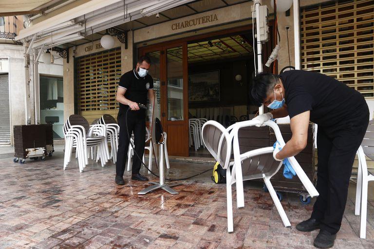 Dos empleados de una cafetería de Málaga preparan el lunes la terraza para poder abrir al público.