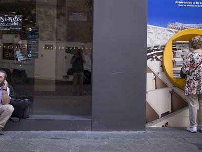 Una persona habla por teléfono mientras espera para poder utilizar un cajero automático en Sevilla.
