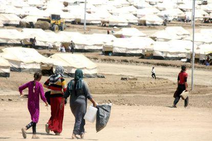 Varias mujeres se dirigen a recoger agua en un campo de refugiados cerca del puesto fronterizo de Zajo, al norte de Irak hoy,.