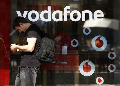 Un hombre consulta su teléfono junto a una tienda de Vodafone.