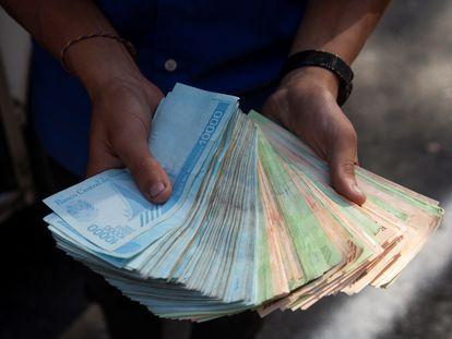 Un transportista muestra un fajo de bolívares, el 12 de marzo de 2021, en Caracas, cuando una barra de pan costaba un millón de bolívares.