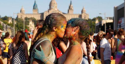 Dos jóvenes se dan un beso en la manifestación del Orgullo en Barcelona.