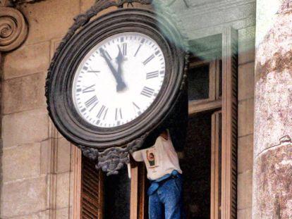 Un operario cambia la hora de un reloj del Ayuntamiento  de Barcelona.
