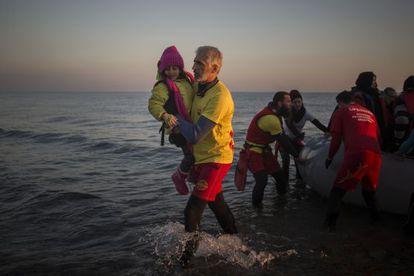 Enrique Álvarez ayuda a bajar a una niña refugiada en una playa cercana a la ciudad de Mytilene, en la isla de Lesbos (Grecia), en 2015.