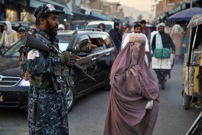 Una mujer, junto a un militar talibán, en el centro de Kandahar (Afganistán).