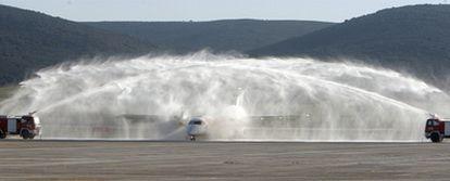 Dos camiones de bomberos bautizan el primer avión que operó en el aeropuerto Central de Ciudad Real.