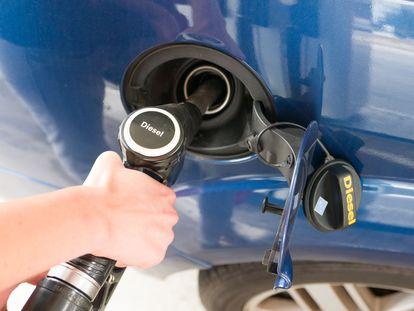 Un conductor reposta combustible diésel en una gasolinera.