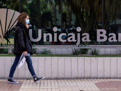 Una mujer pasea ante la sede de Unicaja en Málaga.