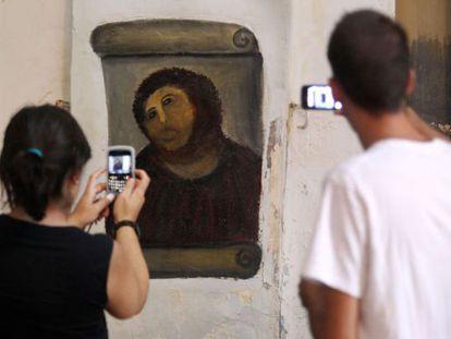 Dos visitantes fotografían el eccehomo de Borja.