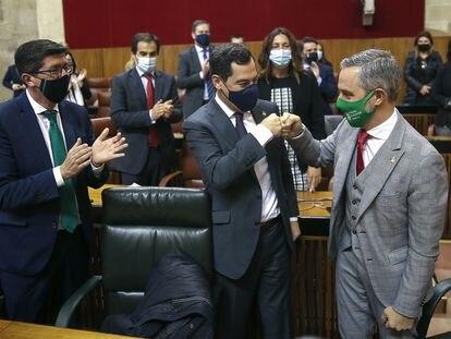 El presidente andaluz, Juanma Moreno (centro) felicita al consejero de Hacienda, Juan Bravo (derecha), ante el vicepresidente, Juan Marín (izquierda), este miércoles.