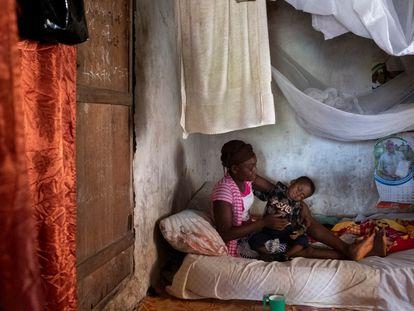 Una adolescente, beneficiaria del proyecto 'Derecho a ser niña', de Save the Children, posa junto a su hijo en su casa del distrito de Pujehun (Sierra Leona).