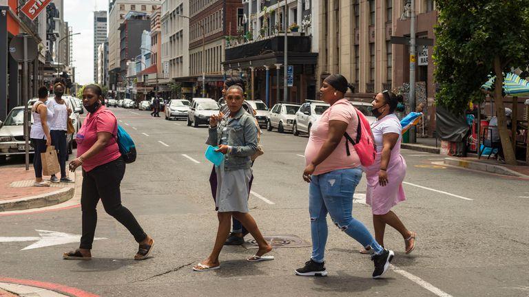 Un grupo de mujeres sin mascarilla cruza Long Street en Ciudad del Cabo, Sudáfrica, en diciembre de 2020, al comienzo de la segunda ola de covid-19 en este país.