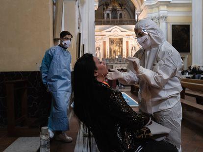 Una vecina del barrio de Sanità, en Nápoles, se somete a una PCR en una iglesia.