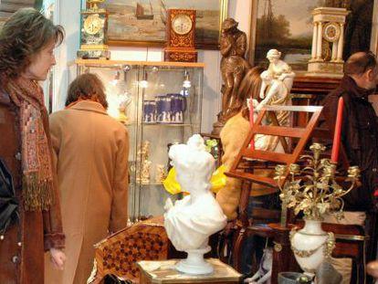 Una mujer mira los objetos de uno de los puestos de la Fira de Brocanters.