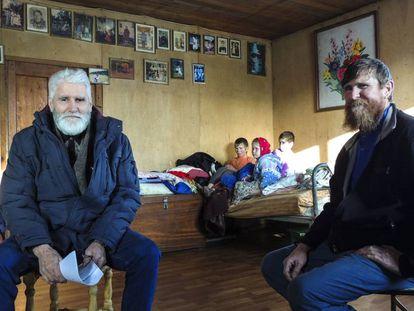 Fedor Kronikovski (a la izquierda) conversa con Ulián Murashov (derecha). Al fondo, los dos hijos de la familia, Agripina y Filaret, junto a otro niño.