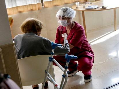Una empleada conversa con una mujer mayor en la residencia de ancianos Santa María de Montecarmelo, en Madrid.