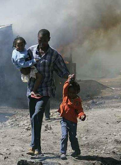 Un hombre y sus hijos entre los incendios en un suburbio de Nairobi.