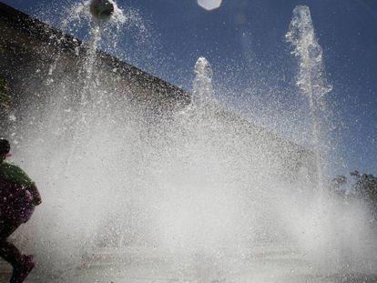 Un niño se divierte con el agua de una fuente de Pamplona.