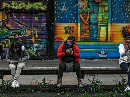 Tres mujeres revisan su móvil en una calle en Bogotá, este martes.