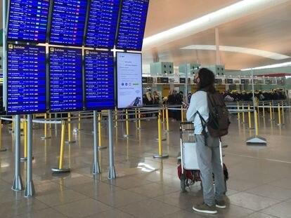 Un pasajero mira los paneles informativos hoy en la T-1 del aeropuerto de El Prat.