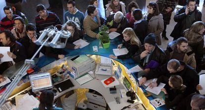 Viajeros afectados por la huelga de controladores reclaman en el mostrador del aeropuerto de Manises (Valencia).