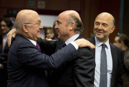 El ministro francés de Finanzas, Michel Sapin, saluda al español Luis de Guindos. A la derecha, el comisario Pierre Moscovici