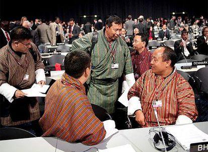 Representantes de 192 países asisten desde el 7 al 18 de de diciembre en Copenhague (Dinamarca) a la 15ª Conferencia de las Partes de la Convención de la ONU sobre Cambio Climático (COP15) que debe alumbrar el futuro acuerdo mundial de reducción de emisiones de CO2. El nuevo texto debe que sustituir al Protocolo de Kioto a partir de 2013 para hacer frente al calentamiento global. En la imagen, delegados de Bután convesan a su llegada al centro de congresos Bella Center, donde se celebra el evento.