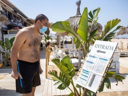 Un turista lee las instrucciones de la covid-19 antes de entrar en el chiringuito Palapa Beach en Valdelagrana  Puerto de Santa María (Cádiz). En vídeo, la situación de los chiringuitos en la Costa del Sol. JUAN CARLOS TORO