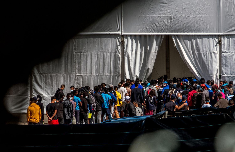 Migrantes del campo oficial de Las Raíces, Tenerife, hacen cola para recibir la comida. JAVIER BAULUZ