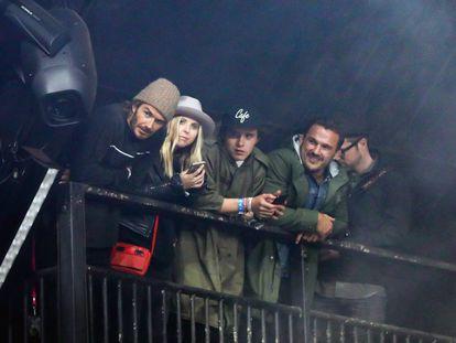 David Beckham, con gorro de lana, y su hijo Brooklyn, con gorra, acompañados de dos amigos viendo a Foo Fighters en Glastonbury.