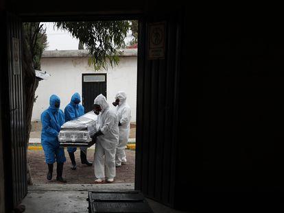 Trabajadores de un crematorio cargan un ataúd en el municipio de Ecatepec, en el Estado de México.