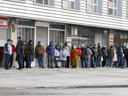 Varias personas forman una larga cola ante una oficina de empleo