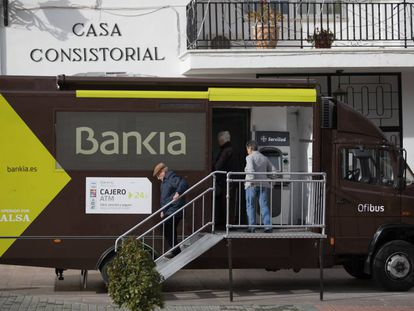 Varios vecinos acuden a la sede bancaria móvil de Bankia, en Corpa (Madrid).
