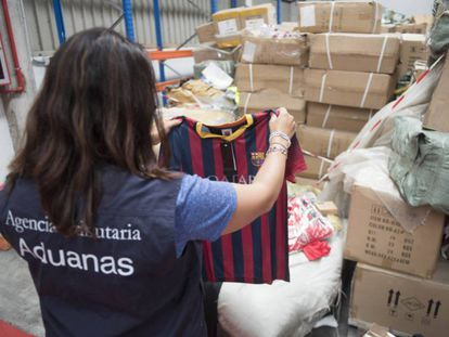 Una agente de Vigilancia Aduanera muestra algunos de los productos falsificados.