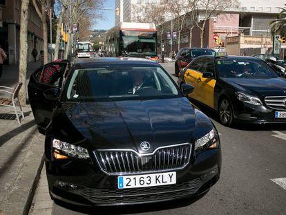 Un usuario de Cabify junto a un taxi, en Barcelona.
