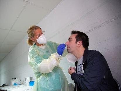 Una sanitaria realiza un test de antígenos o una PCR a un hombre en el Hospital Perpetuo Socorro de Badajoz.