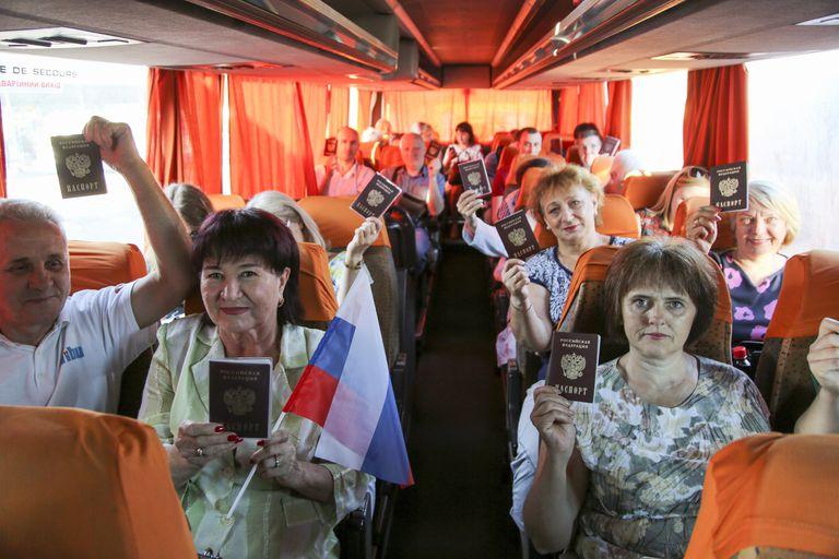 Habitantes de la región de Donetsk mostraban el pasado sábado sus pasaportes rusos en el autobús de camino a Rusia.