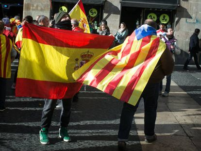 Un ciudadano con una bandera estelada colgada del cuello cruza la plaza Sant Jaume junto a otras personas que portan banderas españolas, en Barcelona.