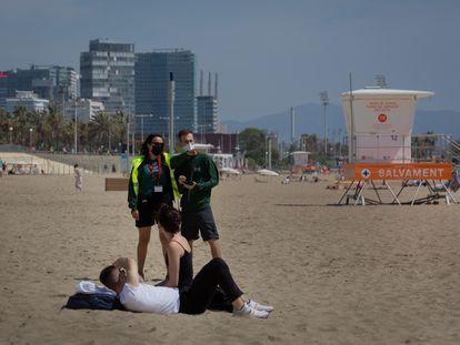 Dos trabajadores del Ayuntamiento de Barcelona controlan el aforo de la playa del Bogotell, el pasado día 6.