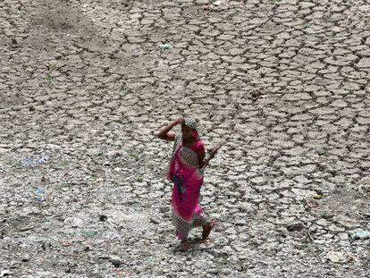 Una mujer camina por una zona seca del río Sabarmati, en un caluroso día en Ahmedabad (India).