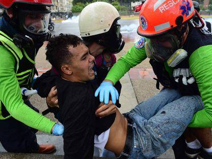 Miembros de la oposición trasladan a un herido.